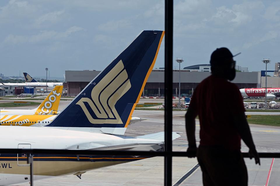 A Singapore Airlines plane is parked besides a Scoot passenger plane on the terminal tarmac at Changi International Airport in Singapore on March 15, 2021. (Photo by Roslan RAHMAN / AFP) (Photo by ROSLAN RAHMAN/AFP via Getty Images)