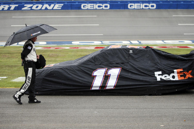 An official walks by the car of Denny Hamlin (11) car during a rain delay in a NASCAR Cup Series auto race at Talladega Superspeedway, Sunday, Oct. 13, 2019, in Talladega, Ala. (AP Photo/Butch Dill)