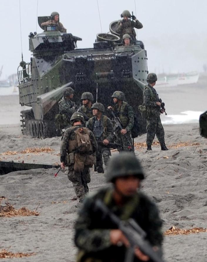 Philippine Marines take positions next to a US Marine amphibious assault vehicle (AAV) during a mock beach assault in 2014 (AFP Photo/Ted Aljibe)