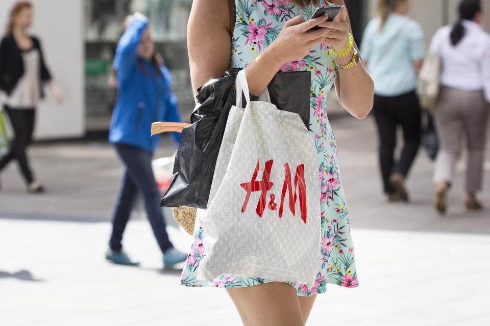 Wiesbaden, Germany - July 28, 2015: An unrecognisable female pedestrian with a plastic bag of Hennes and Mauritz  walking by in a shopping street in the city center of Wiesbaden. H and M (full name: Hennes and Mauritz) is a Swedish retail-clothing company.