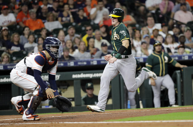 Oakland Athletics' Sean Murphy, right, scores as Houston Astros catcher Robinson Chirinos waits for the throw during the first inning of a baseball game Tuesday, Sept. 10, 2019, in Houston. (AP Photo/David J. Phillip)
