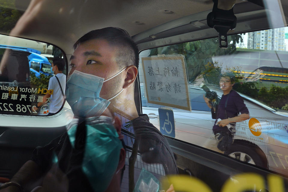 FILE - In this July 6, 2020, file photo, Tong Ying-kit arrives at a court in a police van in Hong Kong. Tong, accused of driving a motorcycle into police officers while carrying a Hong Kong protest flag became on Wednesday, June 23, 2021 the first person to stand trial under the national security law implemented last year as China's central government tightened control over the city. (AP Photo/Vincent Yu, File)