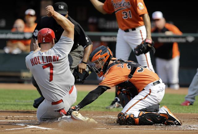 Baltimore Orioles catcher Caleb Joseph, right, tags out St. Louis Cardinals' Matt Holliday in the first inning of an interleague baseball game, Saturday, Aug. 9, 2014, in Baltimore. (AP Photo/Patrick Semansky)