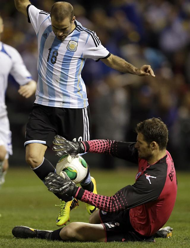 Bosnia goalkeeper Asmir Begovic, bottom, deflects the ball away from Argentina's Rodrigo Palacio during the first half of an international friendly soccer match Monday, Nov. 18, 2013, in St. Louis. Argentina won 2-0. (AP Photo/Jeff Roberson)
