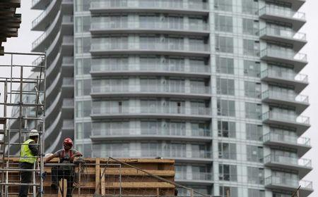 Construction workers chat on a condominium building site in Toronto