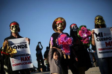 Activists take part in a march to protest violence against women and the murder of a 16-year-old girl in a coastal town of Argentina last week, at Revolucion monument, in Mexico City, Mexico, October 19, 2016. REUTERS/Edgard Garrido