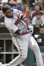 Minnesota Twins' Nelson Cruz hits a broken bat, sacrifice fly, scoring Gilberto Celestino during the eighth inning of a baseball game against the Chicago White Sox. Monday, July 19, 2021, in Chicago. The Twins won the first game of a double-header 3-2. (AP Photo/Charles Rex Arbogast)