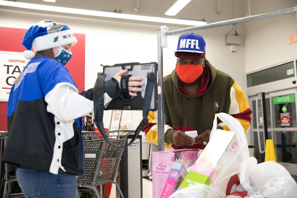 A Burlington Coat Factory shopper in Dallas reacts to having his layaway balance cleared by Dallas Mavericks star Dwight Powell. (Photo: Courtesy of Pay Away the Layaway)