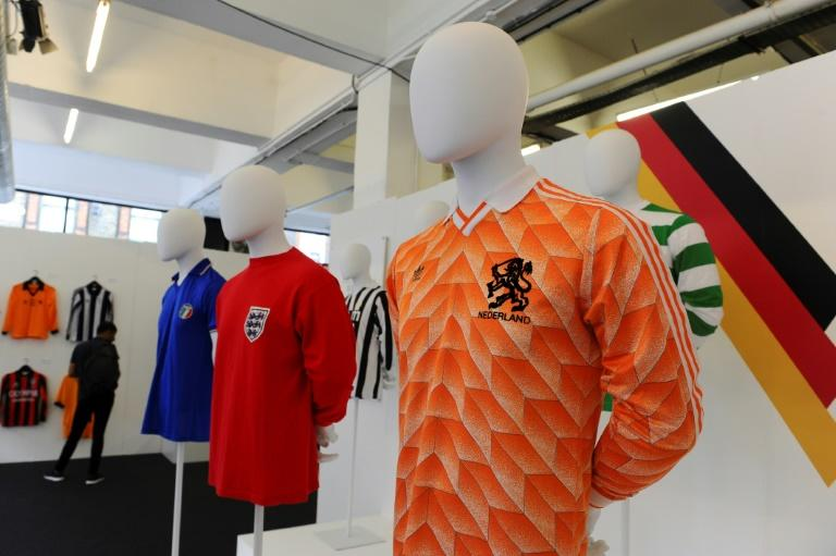 (From L) A football shirt from Italy, from the 80s, an England away shirt from 1966 and a Netherlands shirt from 1988, seen at 'The Art of the Football Shirt' exhibition in London, on July 26, 2017