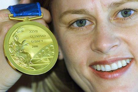 FILE PHOTO - Atlanta hockey gold medallist Danni Roche of Australia holds a display model of a Sydney 2000 Olympic Games gold medal at an unveiling in Sydney, August 12, 2000. REUTERS/Will Burgess/File Photo