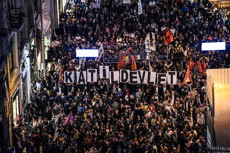 """Signs reading """"Killer state"""" are seen as thousands of protesters take part in a march against the deadly attack earlier in Ankara on October 10, 2015 on Istiklal avenue in Istanbul (AFP Photo/Ozan Kose)"""