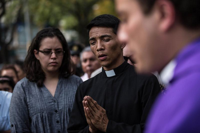 Relatives and friends of victims attend a catholic mass outside the the Enrique Rebsamen school that collapsed during Tuesday's magnitude 7.1 earthquake in Mexico City, Mexico.