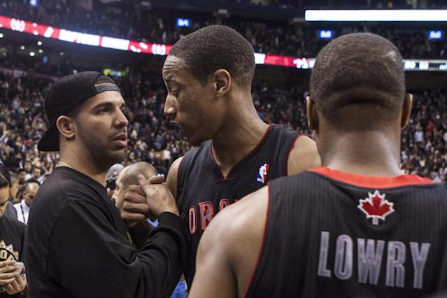 Rapper Drake, left, congratulates Toronto Raptors DeMar DeRozan, center, after his team's 96-80 win over Brooklyn Nets during an NBA basketball game, Saturday, Jan. 11, 2014 in Toronto (AP Photo/The Canadian Press, Chris Young)