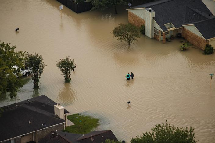 <p>People walk through flooded neighborhoods after Hurricane Harvey dumped up to 50 inches of rain in Houston, Texas, on Aug. 29, 2017. (Photo: Marcus Yam / Los Angeles Times via Getty Images) </p>