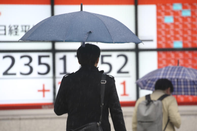 People walk by an electronic stock board of a securities firm in Tokyo, Monday, Dec. 2, 2019. Asian stock markets have risen after Chinese factory activity improved ahead of a possible U.S. tariff hike on Chinese imports. Benchmarks in Shanghai, Tokyo and Hong Kong advanced.  (AP Photo/Koji Sasahara)