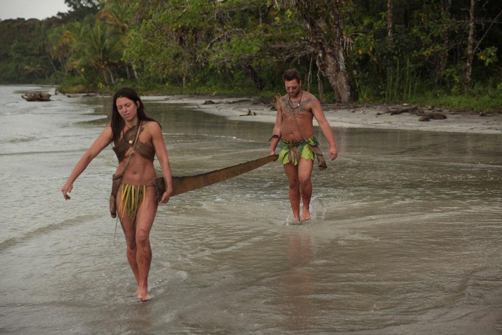 "Clint and Laura carrying wood back to their shelter on Discovery Channel's ""Naked & Afraid."""