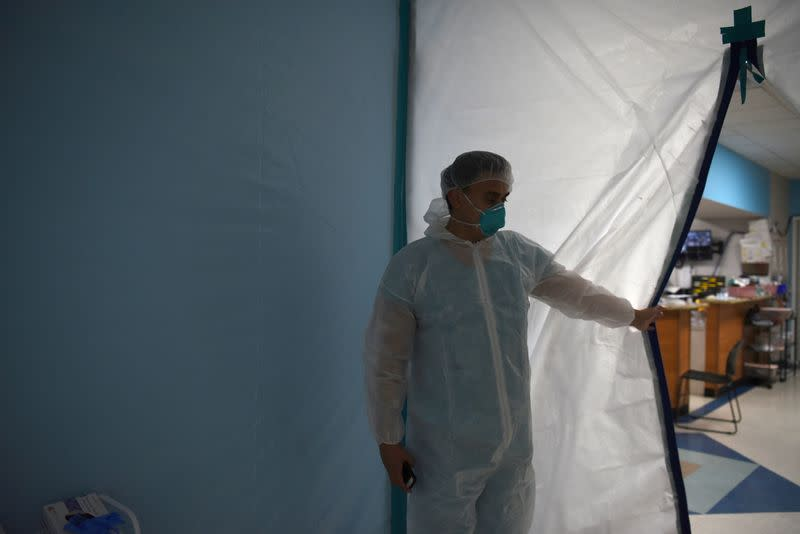 FILE PHOTO: A medical worker opens a makeshift door to the United Memorial Medical Center's coronavirus disease (COVID-19) intensive care unit in Houston