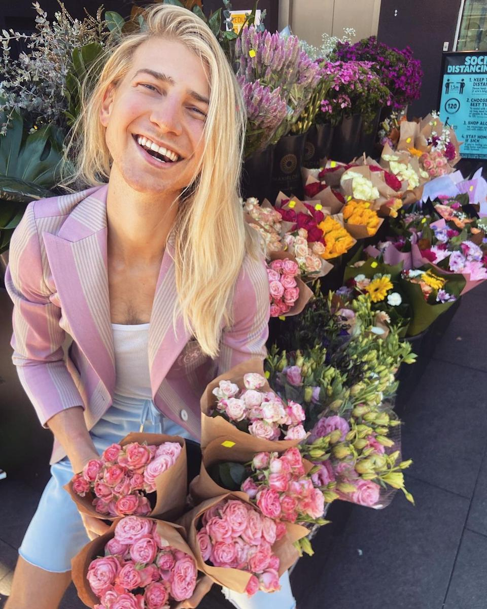 Christian Wilkins holding bunches of roses outside a florist store