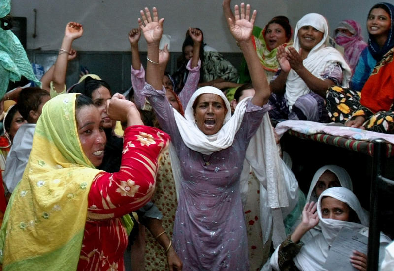 FILE - In this July 8, 2006 file photo, women prisoners celebrate the news of their release on bail, at Adiala Jail in Rawalpindi, Pakistan.  Kanizan Bibi, charged with murdering her employer's wife and five children, remains a prisoner on death row for the last 29 years. She's one of more than 600 mentally ill prisoners in Pakistan's overcrowded prisons.  (AP Photo/Anjum Naveed,file)