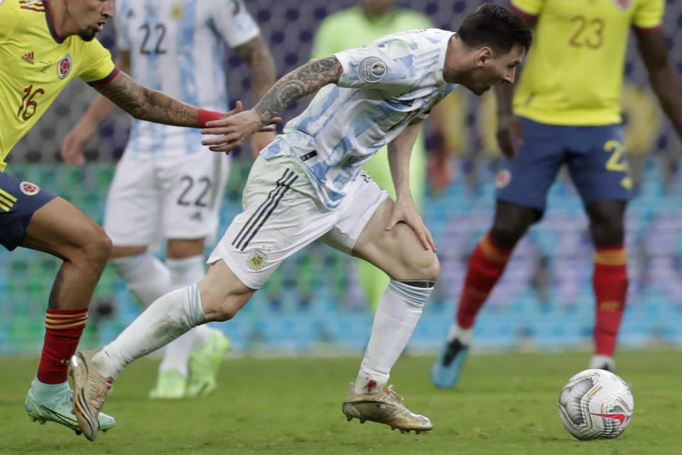 Argentina's Lionel Messi, with a bleeding ankle, battles for the ball with Colombia's Daniel Munoz during a Copa America semifinal soccer match at the National stadium in Brasilia, Brazil, Tuesday, July 6, 2021. (AP Photo/Eraldo Peres)