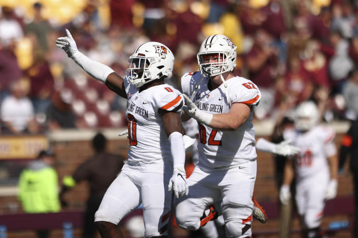 Bowling Green safety Jordan Anderson (0) celebrates with teammate guard Malone VanGorder (62) after winning 14-10 during an NCAA college football game Saturday, Sept. 25, 2021, in Minneapolis. (AP Photo/Stacy Bengs)
