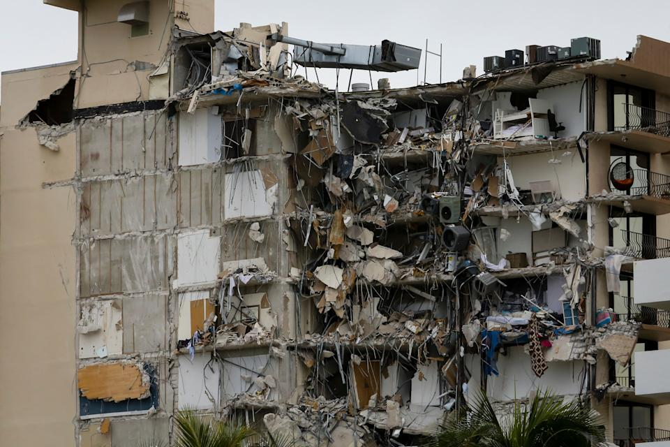 Rubble hangs from a partially collapsed building in Surfside north of Miami Beach, on June 24, 2021. - A high-rise oceanfront apartment block near Miami Beach partially collapsed early JUNE 24, 2021, killing at least one person and leaving 99 unaccounted for, with fears the toll may rise much higher as rescuers comb through the rubble. (Photo by Eva Marie UZCATEGUI / AFP) (Photo by EVA MARIE UZCATEGUI/AFP via Getty Images)