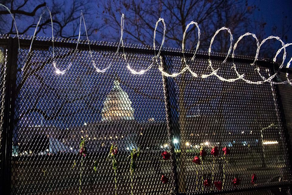 Flowers are placed along the razor wire fencing that now surrounds the U.S. Capitol on Jan. 15. (Photo: Liz Lynch via Getty Images)