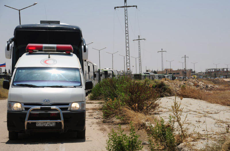 In this photo released by the Syrian official news agency SANA, a convoy of buses carrying opposition fighters and their families leave the southern province of Daraa, Syria, Sunday, July 15, 2018. The evacuation deal will hand over areas held by the rebels for years back to government control. Daraa, which lies on a highway linking Damascus with Jordan, was the cradle of the 2011 uprising against Syrian President Bashar Assad. (SANA via AP)