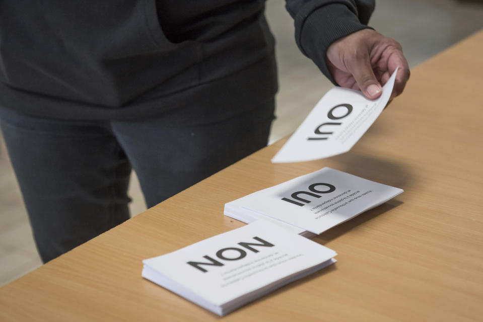 """A person picks up cards of """"Yes"""" and """"No"""" before casting one of them at a referendum in Noumea, New Caledonia, Sunday, Oct. 4, 2020, whether voters choose independence from France. Voters in New Caledonia, a French archipelago in the South Pacific, are deciding Sunday whether they want independence from France in a referendum that marks a milestone in a three-decade decolonization effort. (AP Photo/Mathurin Derel)"""