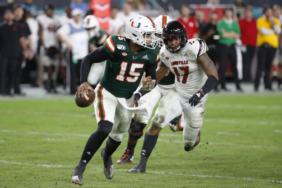 Miami quarterback Jarren Williams (15) scrambles as he is rushed by Louisville linebacker Dorian Etheridge (17) during the second half of an NCAA college football game Saturday, Nov. 9, 2019, in Miami Gardens, Fla. Williams set a school record with six touchdown passes as Miami defeated Louisville 52-27. (AP Photo/Wilfredo Lee)