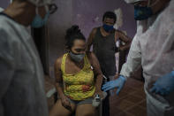 Mobile Emergency Care Service (SAMU) worker Elias Anjo, right, checks a patient suspected of having COVID-19 at her house in Duque de Caxias, Rio de Janeiro state, Brazil, Tuesday, April 6, 2021. (AP Photo/Felipe Dana)