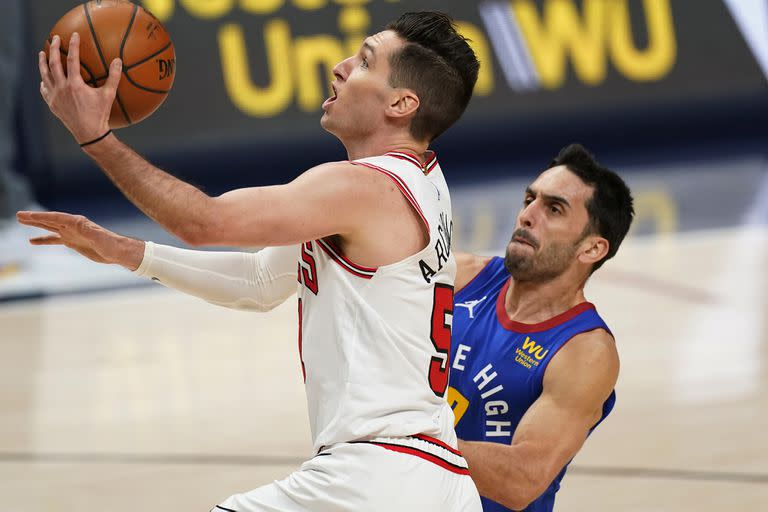 Chicago Bulls guard Ryan Arcidiacono, front, is fouled by Denver Nuggets guard Facundo Campazzo during the first half of an NBA basketball game Friday, March 19, 2021, in Denver. (AP Photo/David Zalubowski)