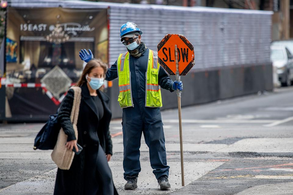 NEW YORK, NEW YORK - MARCH 25: A construction worker directs traffic and wears a mask near Union Square on March 25, 2021 in New York City. After undergoing various shutdown orders for the past 12 months the city is currently in phase 4 of its reopening plan, allowing for the reopening of low-risk outdoor activities, movie and television productions, indoor dining as well as the opening of movie theaters, all with capacity restrictions. (Photo by Roy Rochlin/Getty Images)