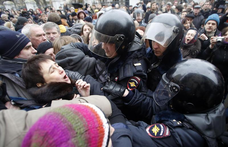 Russian police officers detain opposition activists outside a court room in Moscow, Russia, Monday, Feb. 24, 2014, where hearings started against opposition activists detained on May 6, 2012 during a rally at Bolotnaya Square. A Moscow judge on Friday, Feb. 21, 2014, convicted eight anti-government protesters of rioting during a 2012 protest against Vladimir Putin, following a trial seen as part of the Kremlin's efforts to stifle dissent. (AP Photo/Denis Tyrin)