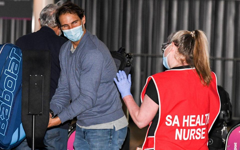 Spanish tennis player Rafael Nadal gets a wave from a nurse as he arrives before heading straight to quarantine for two weeks isolation ahead of their Australian Open warm up matches in Adelaide on January 14, 2021. - AFP/BRENTON EDWARDS