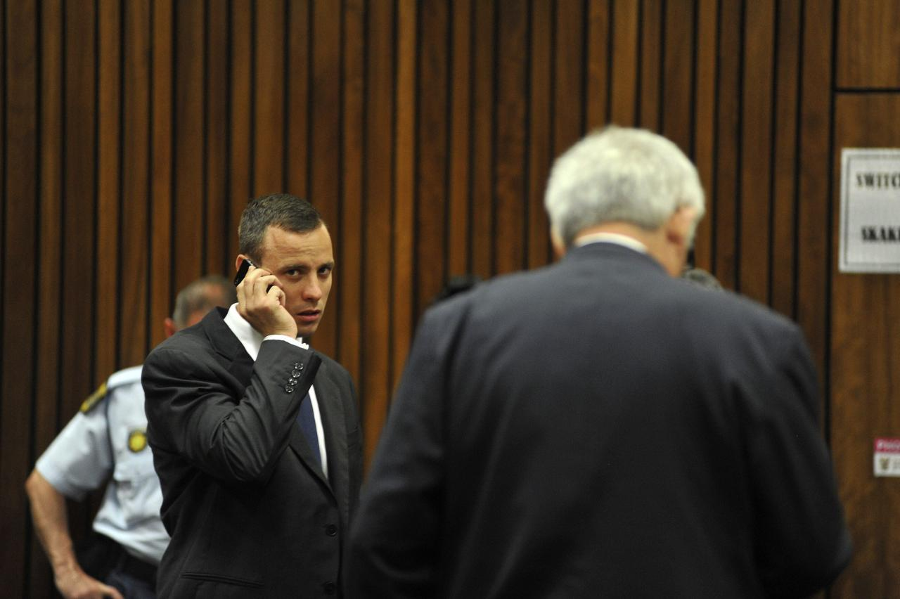 """Olympic and Paralympic track star Oscar Pistorius talks on a mobile phone as he makes his way to the dock in the North Gauteng High Court in Pretoria March 24, 2014. The track star, nicknamed the """"Blade Runner"""", is on trial for the murder of his girlfriend Reeva Steenkamp at his suburban Pretoria home on Valentine's Day last year. He has pleaded not guilty, saying he mistook Steenkamp for an intruder. REUTERS/Ihsaan Haffejee/Pool (SOUTH AFRICA - Tags: SPORT CRIME LAW ATHLETICS)"""