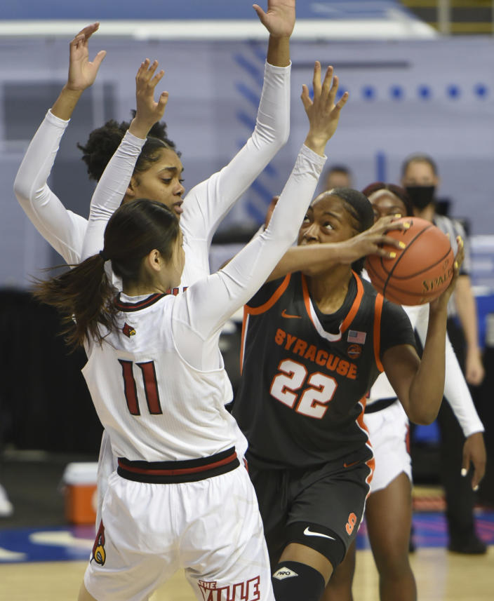 Syracuse's Amaya Finklea-Guity looks for a shot under pressure from Louisville's Ramani Parker and Norika Konno (11) during an NCAA college basketball game in the semifinals of Atlantic Coast Conference tournament in Greensboro, N.C., Saturday, March 6, 2021. (Walt Unks/The Winston-Salem Journal via AP)