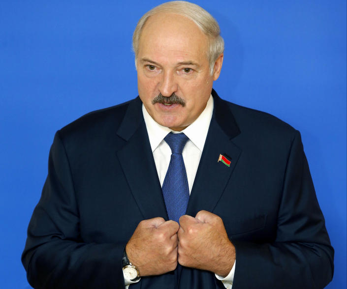 FILE - In this Sunday, Oct. 11, 2015, file photo Belarusian President Alexander Lukashenko speaks to the media at a polling station after voting during the presidential election in Minsk, Belarus. Belarus' authoritarian President Alexander Lukashenko faces a perfect storm as he seeks a sixth term in the election held Sunday, Aug. 9, 2020 after 26 years in office. (AP Photo/Sergei Grits, File)