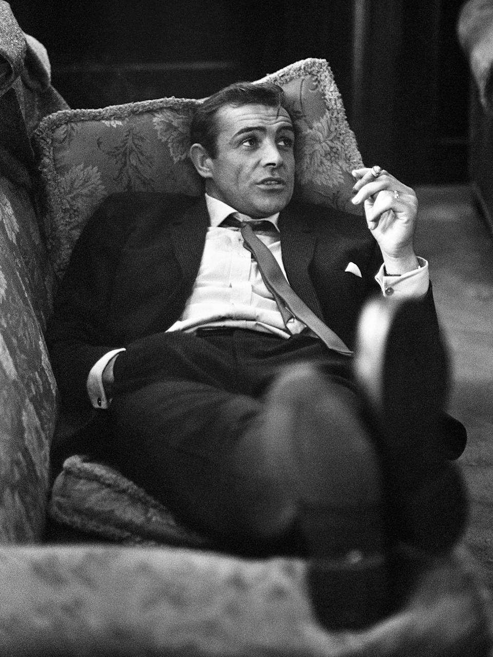 <p>Connery lounges on a sofa with a cigarette during the filming of 'Woman of Straw' in 1963</p>Getty