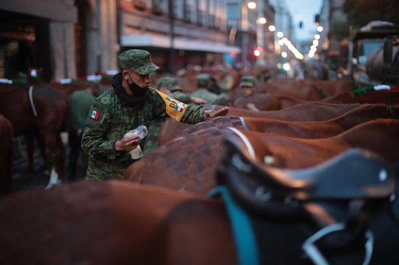 VARIOUS CITIES, MEXICO - SEPTEMBER 16: A Mexican soldier prepares the horses during the Independence Day military parade at Zocalo Square on September 16, 2020 in Various Cities, Mexico. This year El Zocalo remains closed for general public due to coronavirus restrictions. Every September 16 Mexico celebrates the beginning of the revolution uprising of 1810. (Photo by Hector Vivas/Getty Images)