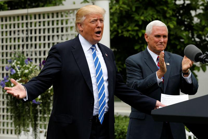 Trump, flanked by Pence, takes the stage to deliver remarks to members of the Independent Community Bankers Association at the White House in Washington