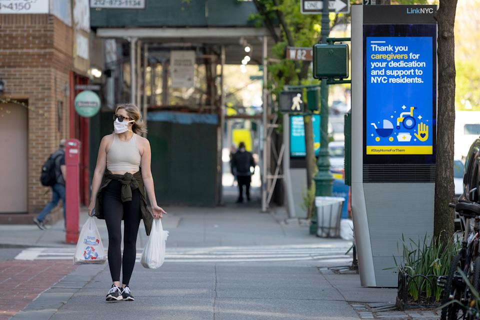 NEW YORK, NEW YORK - APRIL 28: A woman wearing a protective mask carries groceries while a sign thanks caregivers amid the coronavirus pandemic on April 28, 2020 in New York City, United States. COVID-19 has spread to most countries around the world, claiming over 217,000 lives with over 3.1 million cases. (Photo by Alexi Rosenfeld/Getty Images)