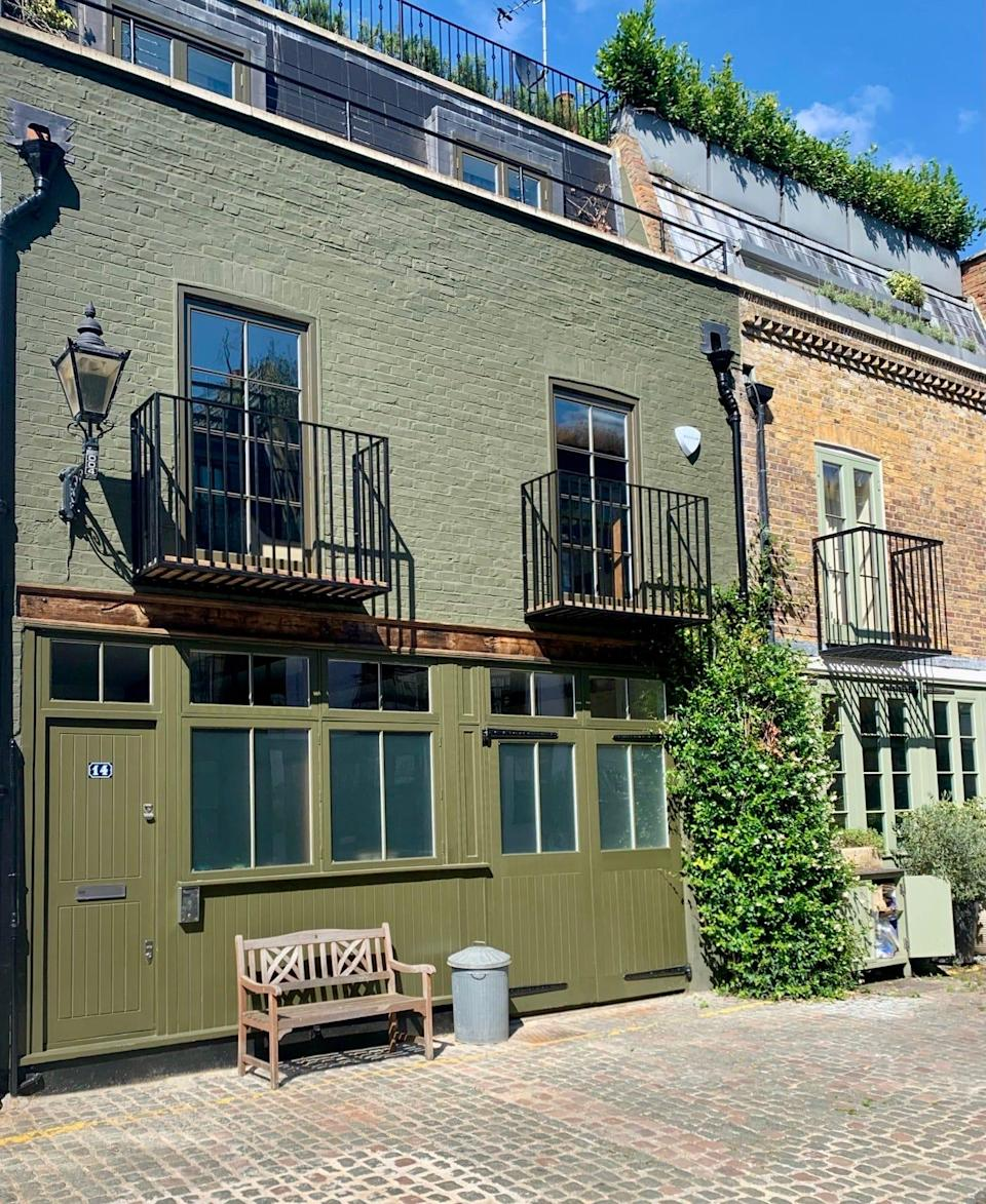 Number 14 St. Lukes Mews is a army green color and has a wooden bench placed out front.