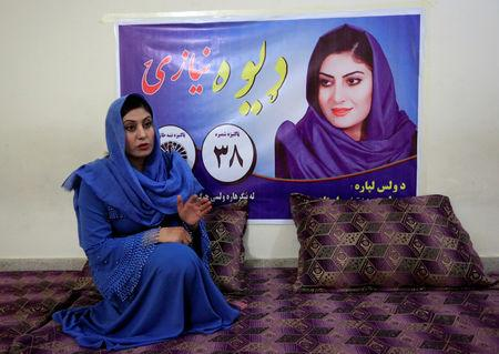 Female Afghan parliamentary election candidate, Dewa Niazai, sits in front of her poster during an election campaign in Jalalabad, Afghanistan October 3, 2018.  REUTERS/Parwiz