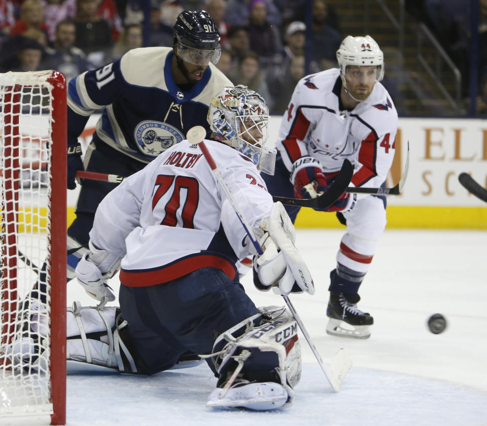 Washington Capitals' Braden Holtby, front, makes a save as teammate Brooks Orpik, right, and Columbus Blue Jackets' Anthony Duclair wait for the rebound during the second period of an NHL hockey game Tuesday, Feb. 12, 2019, in Columbus, Ohio. (AP Photo/Jay LaPrete)