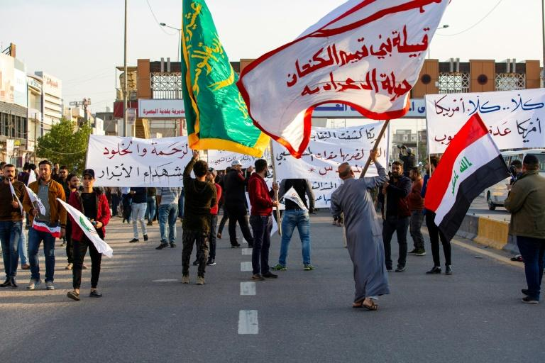 Iraqis wave flags of the Hashed Al-shaabi armed network in Basra during a demonstration to denounce attacks by US planes on several bases belonging to the Hezbollah Brigades (AFP Photo/Hussein FALEH)