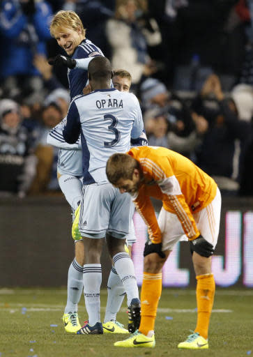 Sporting KC defender Seth Sinovic, top, celebrates with teammates Sporting KC defender Ike Opara (3) and Sporting KC defender Matt Besler, back, following an MLS playoff soccer match in Kansas City, Kan., Saturday, Nov. 23, 2013. Houston defender Eric Brunner, front, stands with his hands on his knees. Sporting KC defeated Houston Dynamo 2-1. (AP Photo/Orlin Wagner)