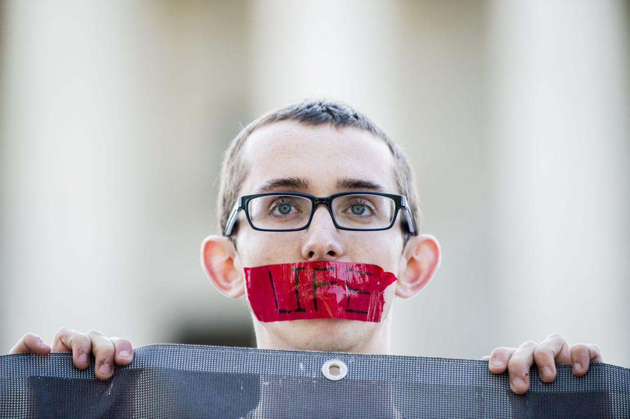 <p>JUN. 27, 2016 — Anti-abortion activist Ryan Orr, 17, of Manassas, Va., holds a silent vigil as he waits for rulings in front of the U.S. Supreme Court. The court handed a victory to abortion rights advocates, striking down a Texas law imposing strict regulations on abortion doctors and facilities (Pete Marovich/Getty Images) </p>