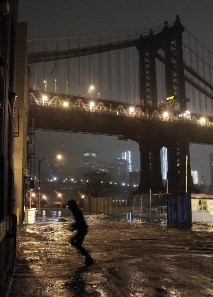 A pedestrian runs through floodwaters in the Dumbo section of the Brooklyn borough of New York, as superstorm Sandy moves through the area, on Monday, Oct. 29, 2012. Sandy zeroed in on New York's waterfront with fierce rain and winds that shuttered most of the nation's largest city Monday, darkened the financial district and left a huge crane hanging off a luxury high-rise. (AP Photo/Bebeto Matthews)