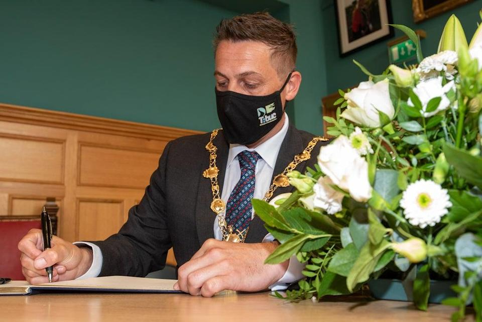 Derry City and Strabane District Council Mayor, Alderman Graham Warke, signs the Book of Condolence for Pat Hume in the Guildhall. Picture Martin McKeown. 03.09.21